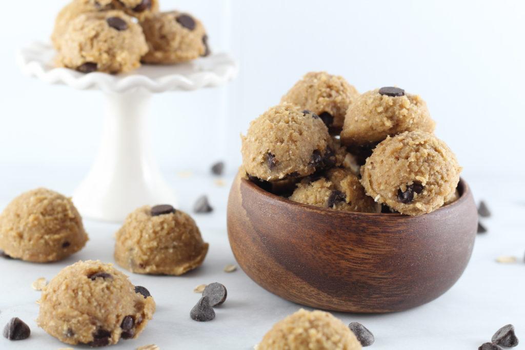 bowl of cookie dough bites and white cupcake pedestal