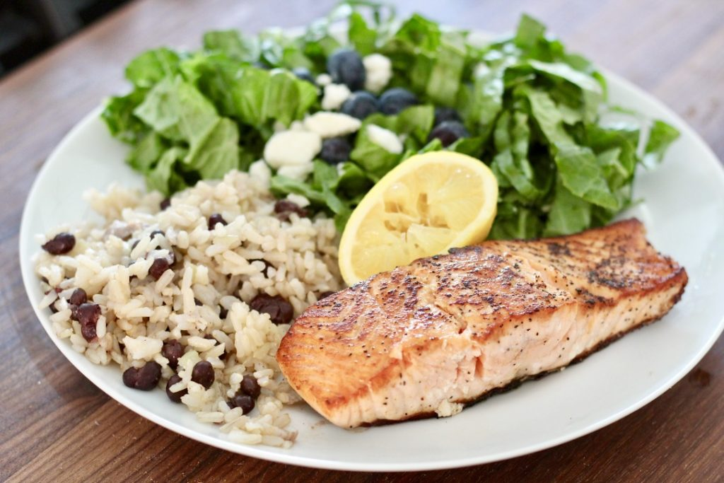 pan fried salmon with rice and salad on white plate how to cook salmon
