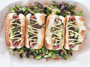 beef hot dogs with toppings on a bed of veggies