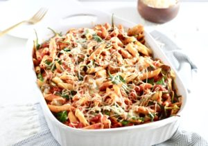 Cheesy Ground Lamb and Spinach Pasta Bake in white baking dish