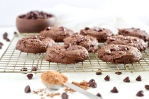 Double Chocolate Fudge Breakfast Cookies on cooling rack with cocoa powder and chocolate chips