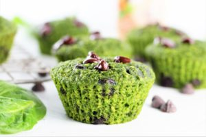 close up image of green oatmeal chocolate chip muffins with basil leaf and chocolate chips on counter