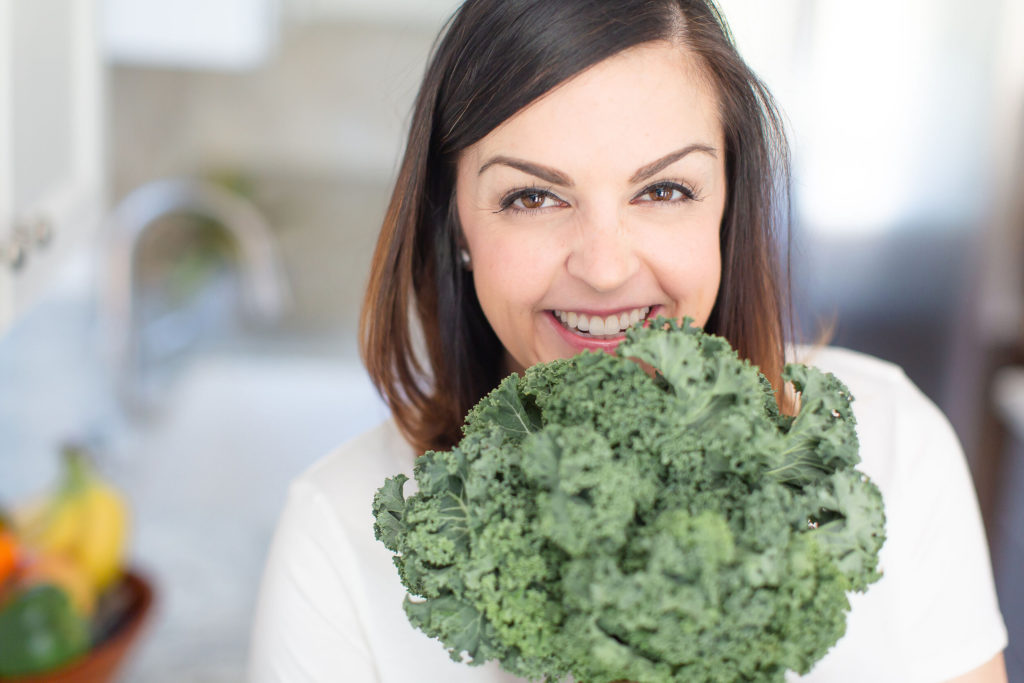 close up picture of Mary Ellen Phipps with a bunch of kale