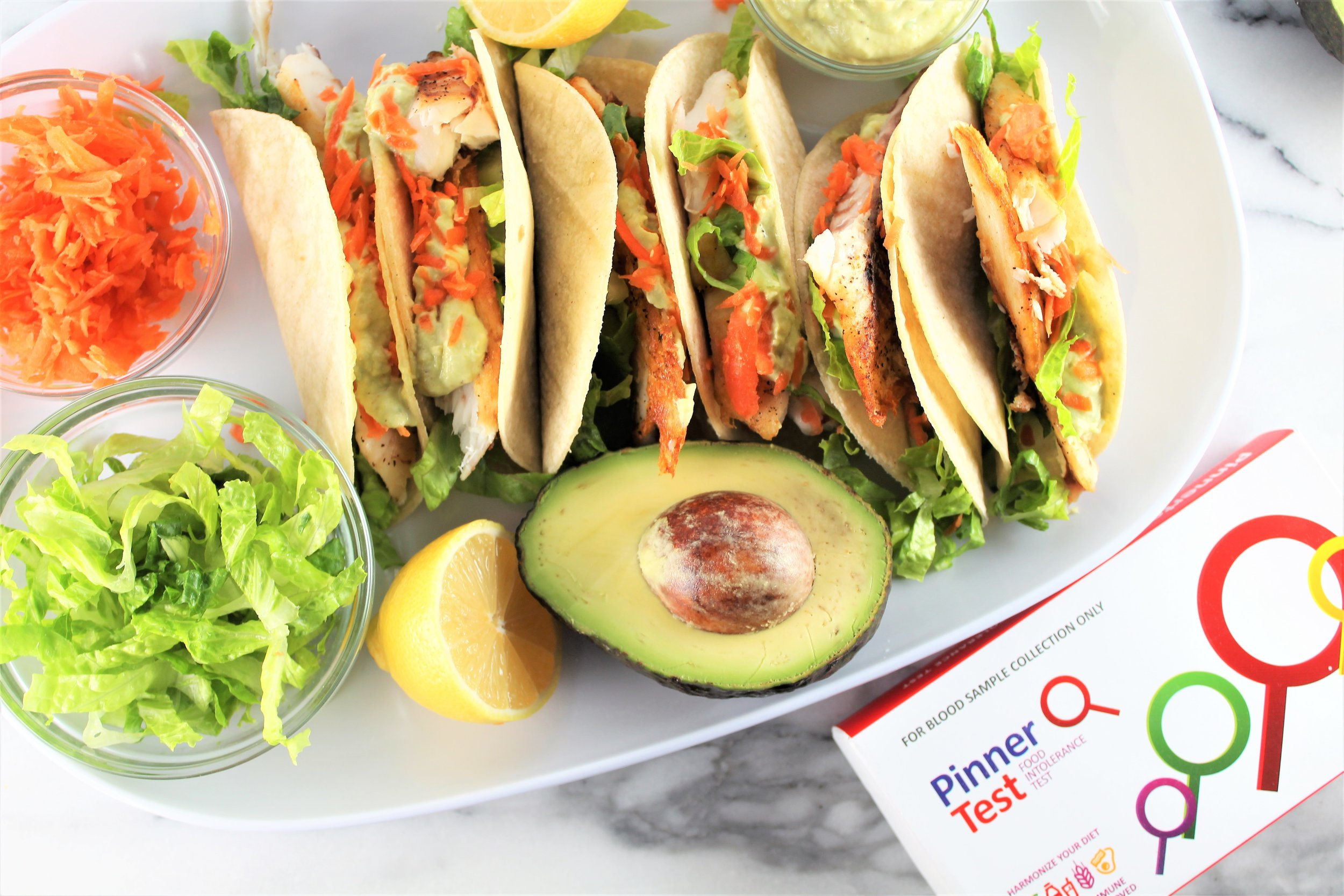 fish tacos with avocado, lettuce, carrots, and pinner test box