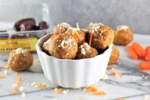 No-Bake Carrot Cake Energy Balls in a bowl with ingredients on counter