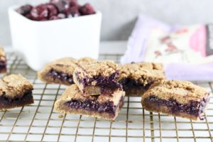 Paleo Blueberry Breakfast Bars on cooling rack with bowl of blueberries and bob's red mill mix