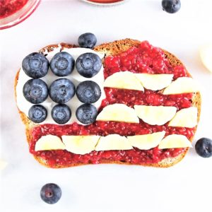 Toast designed in american flag with blueberries, banana, and raspberries