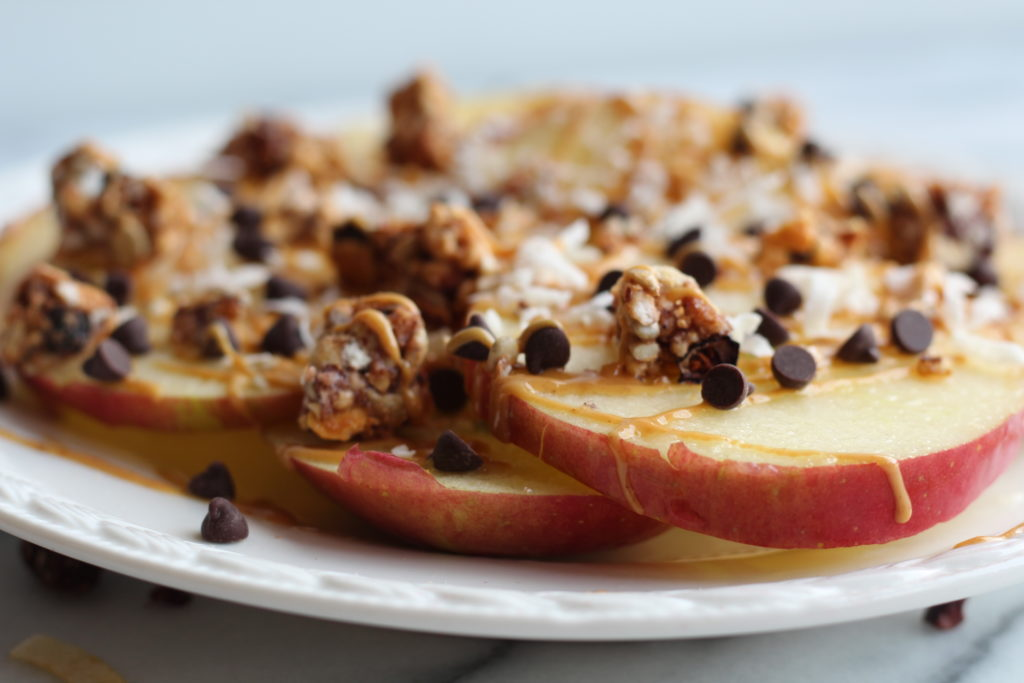 apple nachos on a plate with cacao nibs and peanut butter