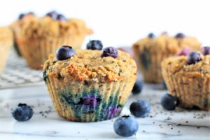 side view of blueberry chia muffins on countertop with blueberries