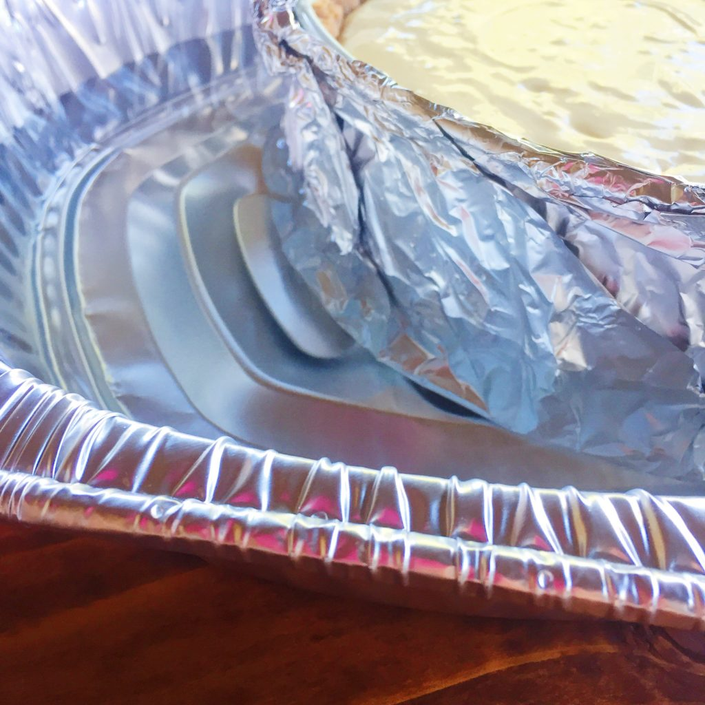 cheesecake making step with layers of aluminum pan