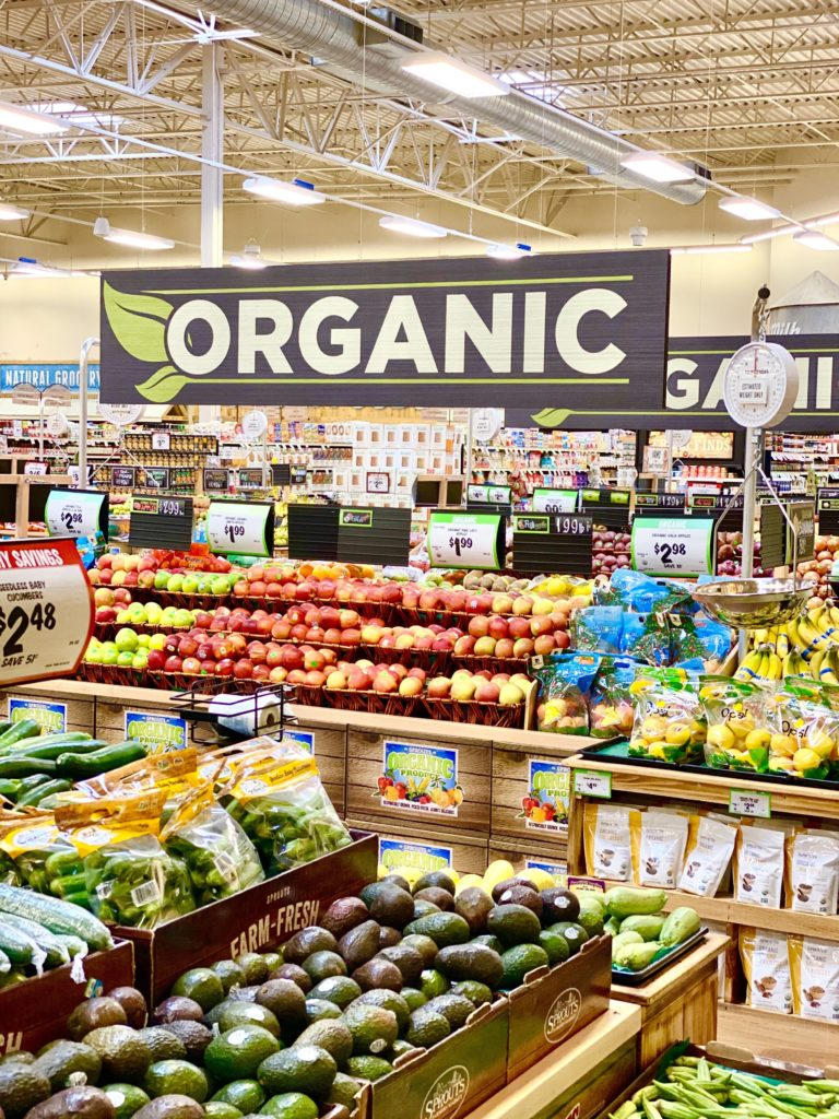 organic produce section at sprouts with apples, avocado, bananas