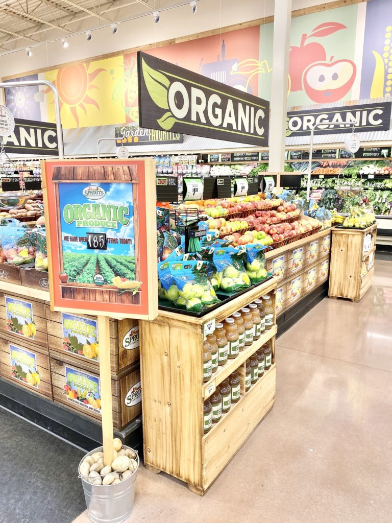 organic produce section sprouts with apples and apple juice and pears
