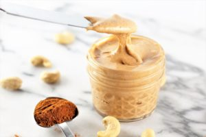 pumpkin spice roasted cashew butter with measurement of pumpkin spice on counter