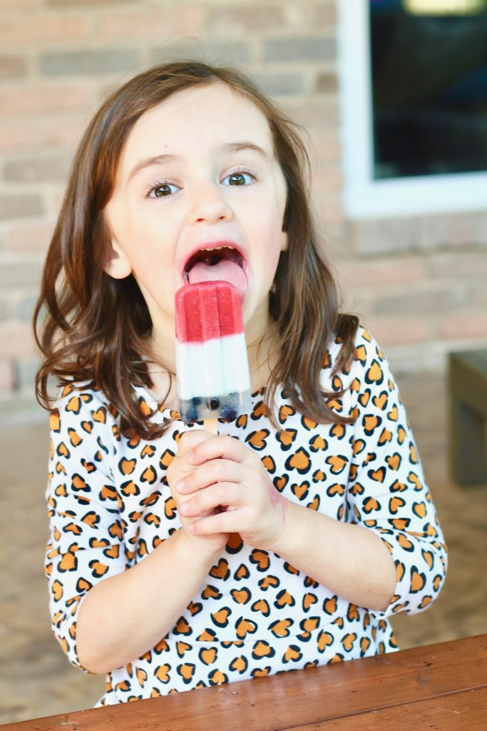 kid eating red white and blue popsicle
