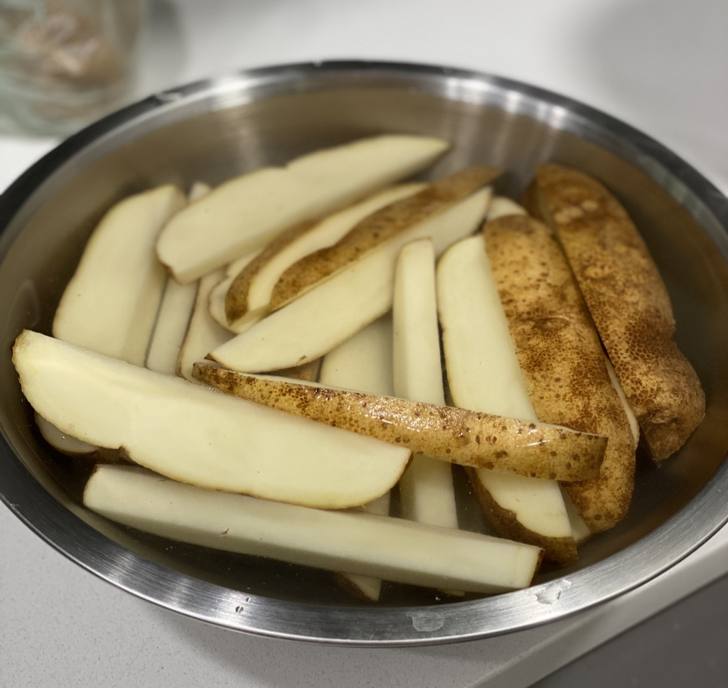 sliced potato wedges in bowl of water