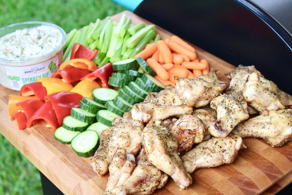 chicken wings and veggies on outdoor grill