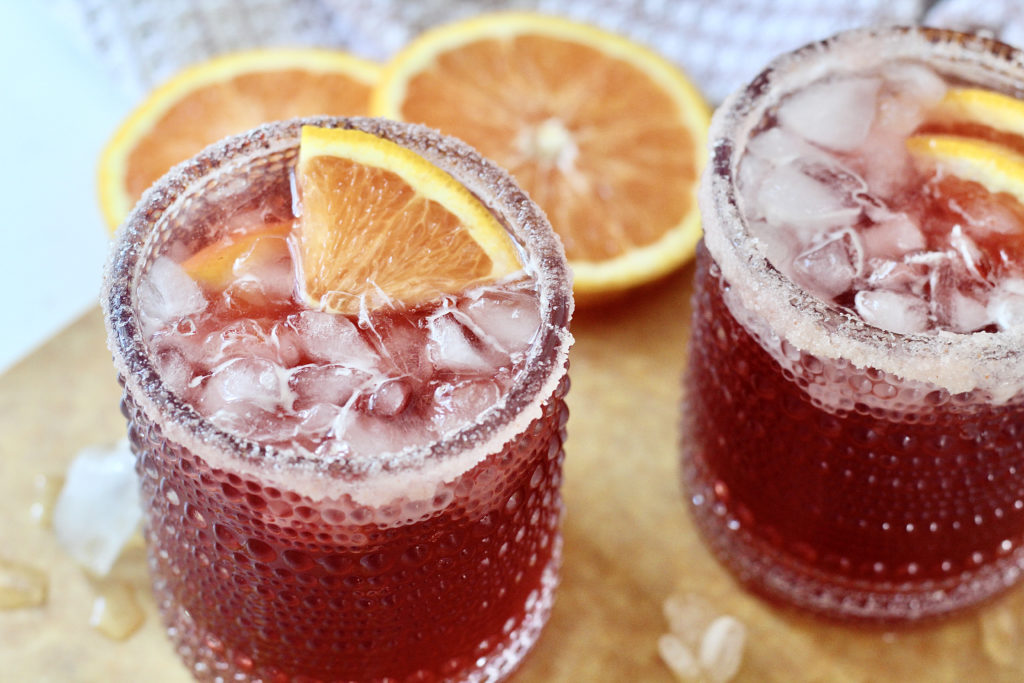 two pomegranate martinis with ice and orange wedges