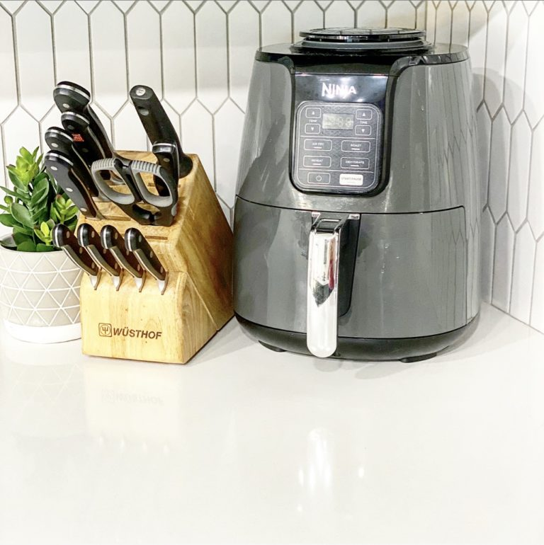 knife block with an air fryer on white quartz countertop
