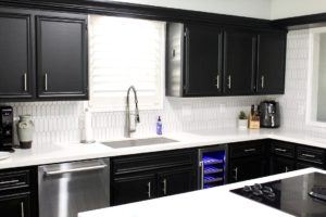 clean kitchen with black cabinets and white countertops