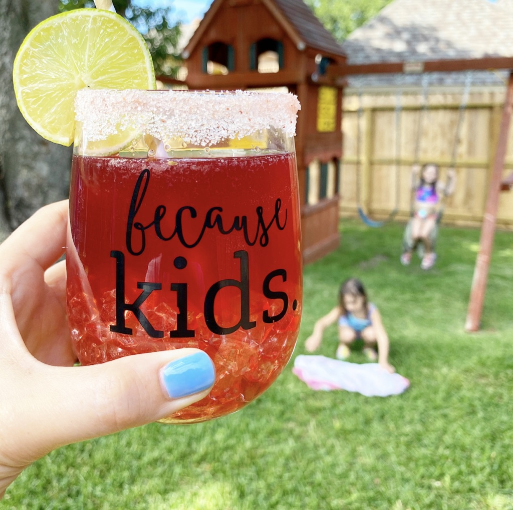 mom holding cocktail with kids playing in background