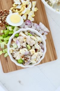 tuna salad on cutting board with hard boiled eggs celery onion and pecans