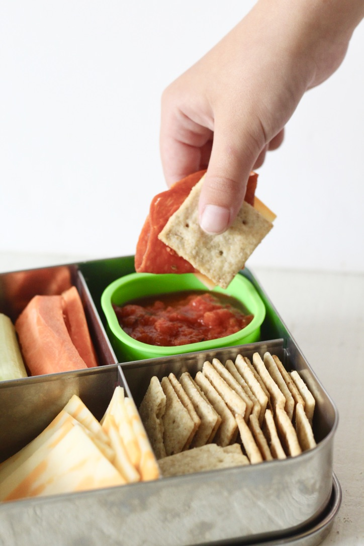 child's hand dipping crackers and pepperoni in pizza sauce for punchable in stainless steel container