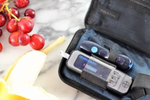 blood glucose meter with bananas and grapes for blood sugar balance