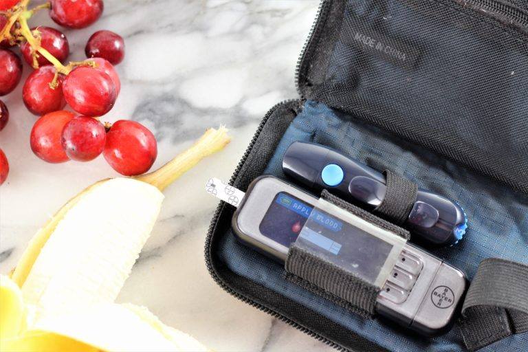 blood glucose meter with bananas and grapes