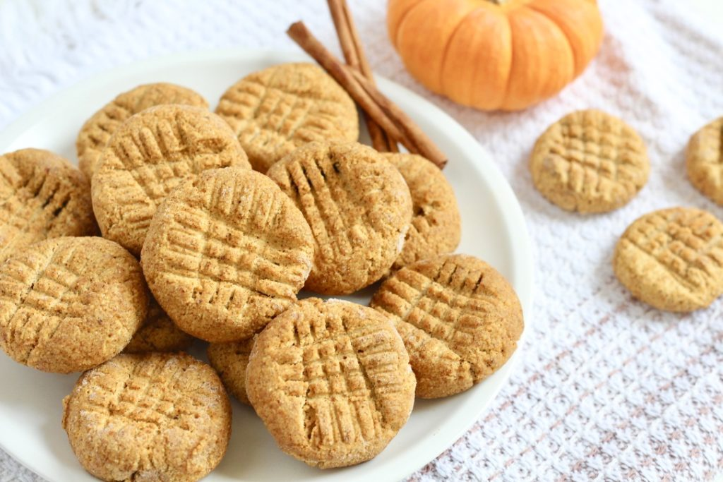 pumpkin cookies on white plate with cinnamon sticks and mini pumpkin
