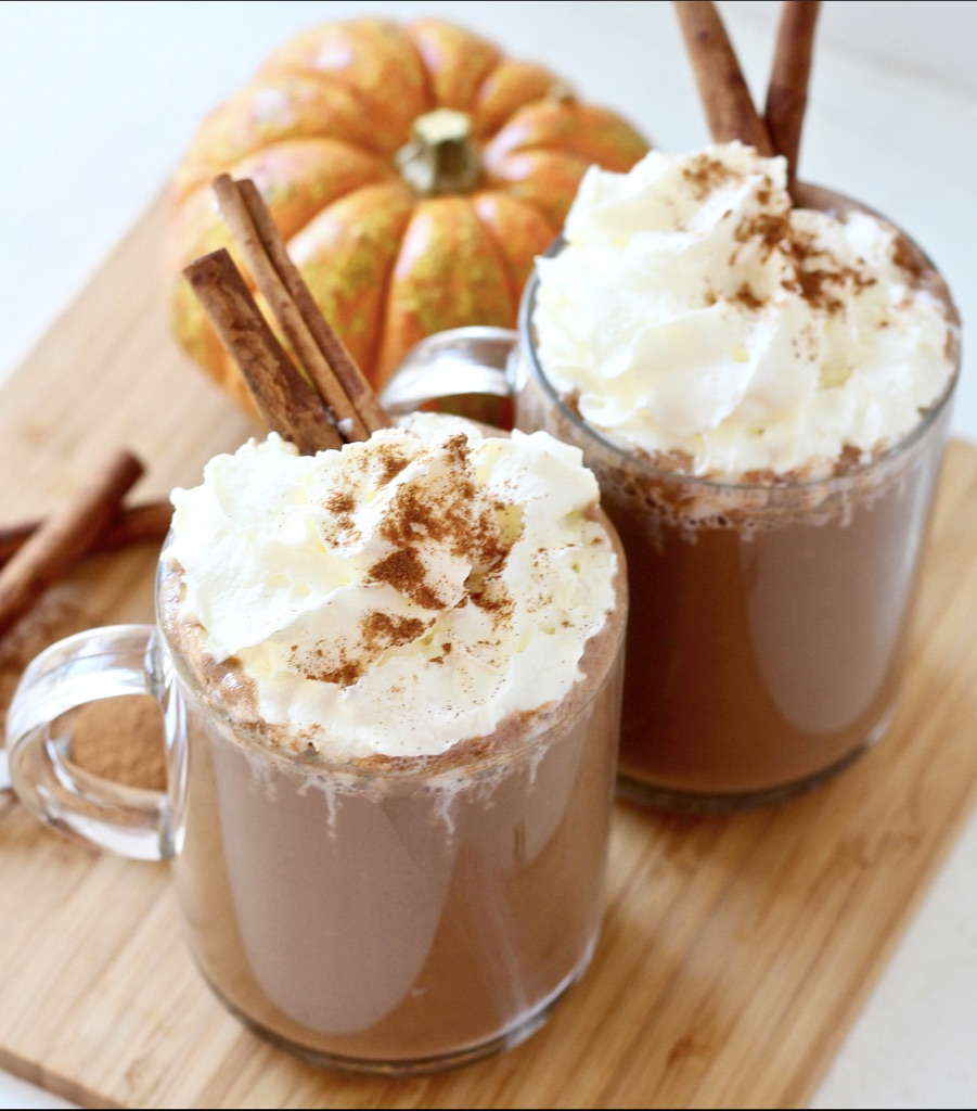 hot chocolate with chipped cream and cinnamon sticks