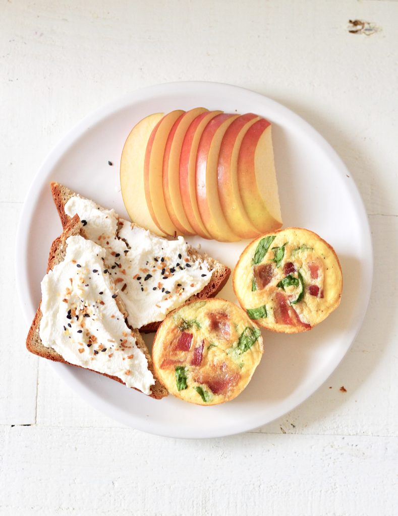 white plate with Starbucks egg bites, toast with ricotta cheese and sliced apples