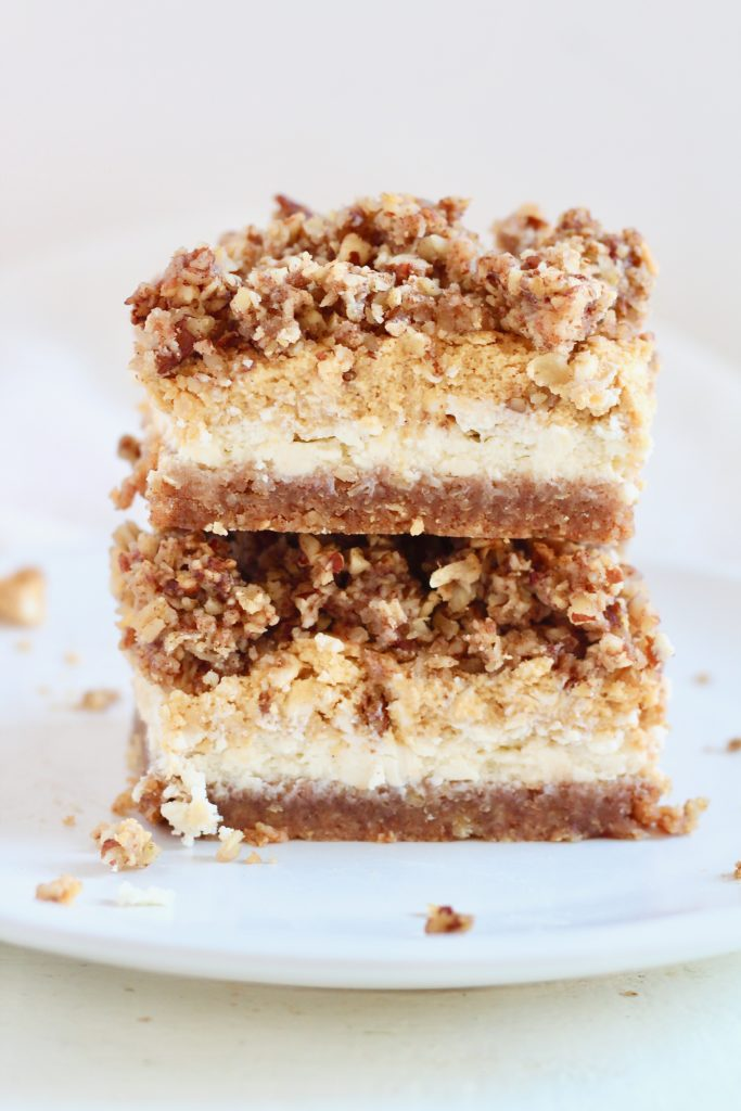layered pumpkin cheesecake bars stacked on top of each other