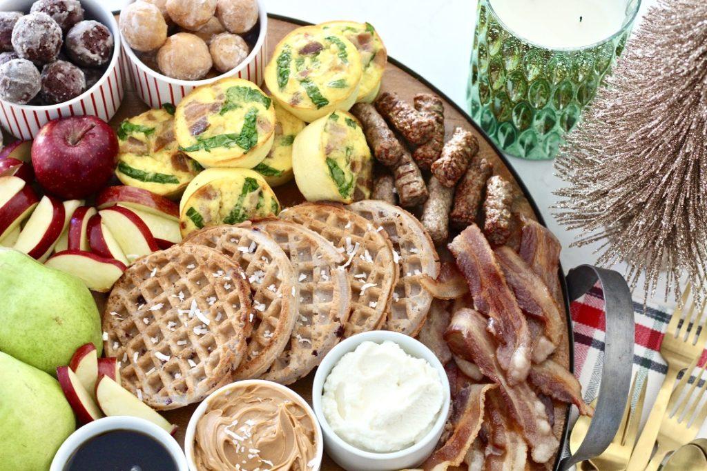 doughnut holes, waffles, and fruit on breakfast board