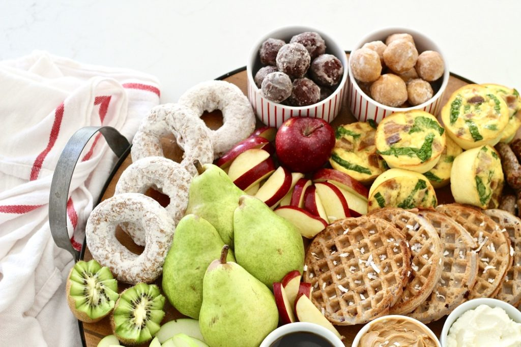 kiwi apples and pears and doughnuts on breakfast board