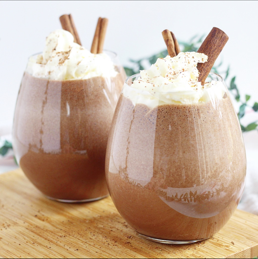 two glasses chocolate eggnog with whipped cream and cinnamon sticks