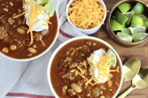 gluten free chili with turkey cheddar cheese and limes in two bowls