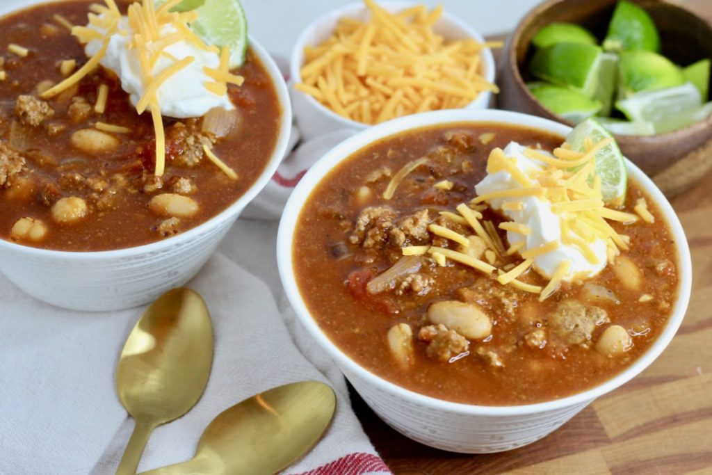 gluten free chili in two bowls with gold spoons
