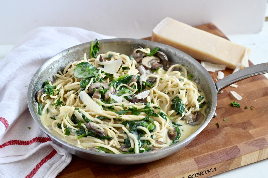 truffle mushroom pasta in stainless steel skillet on wood cutting board with parmesan cheese block