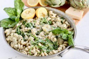 artichoke pesto pasta in stainless steel pan