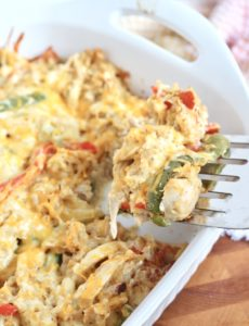 chicken fajita casserole on spatula with white baking dish