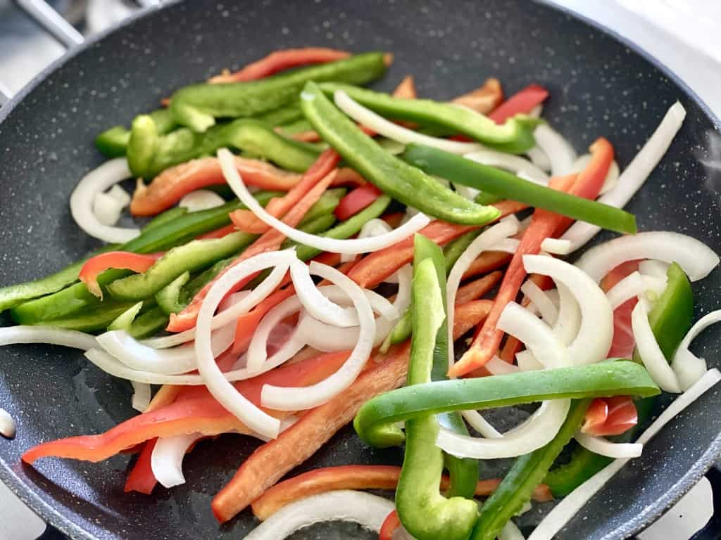 bell peppers and onion in pan for chicken fajita casserole
