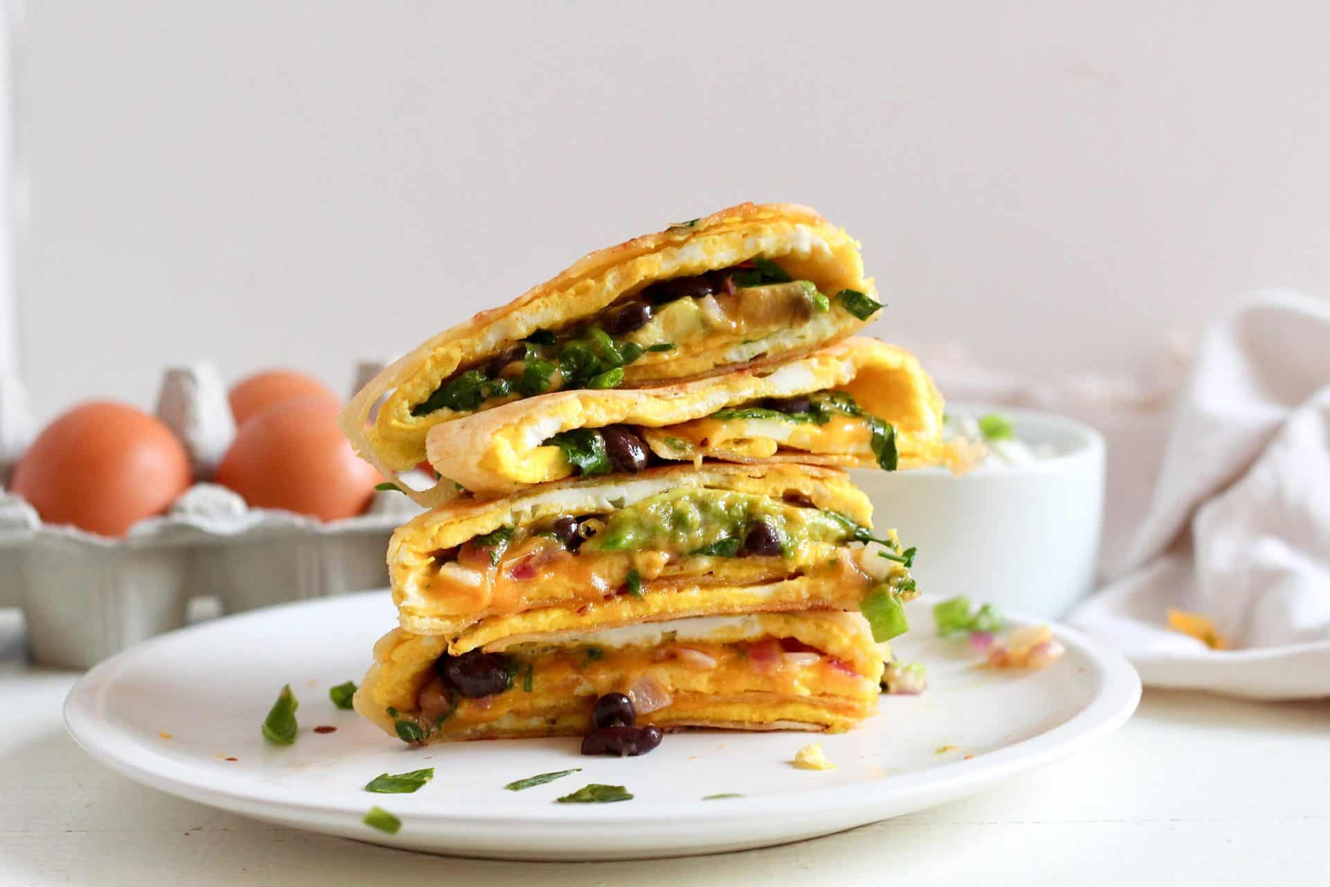 stack of veggie black bean and egg quesadilla on white plate