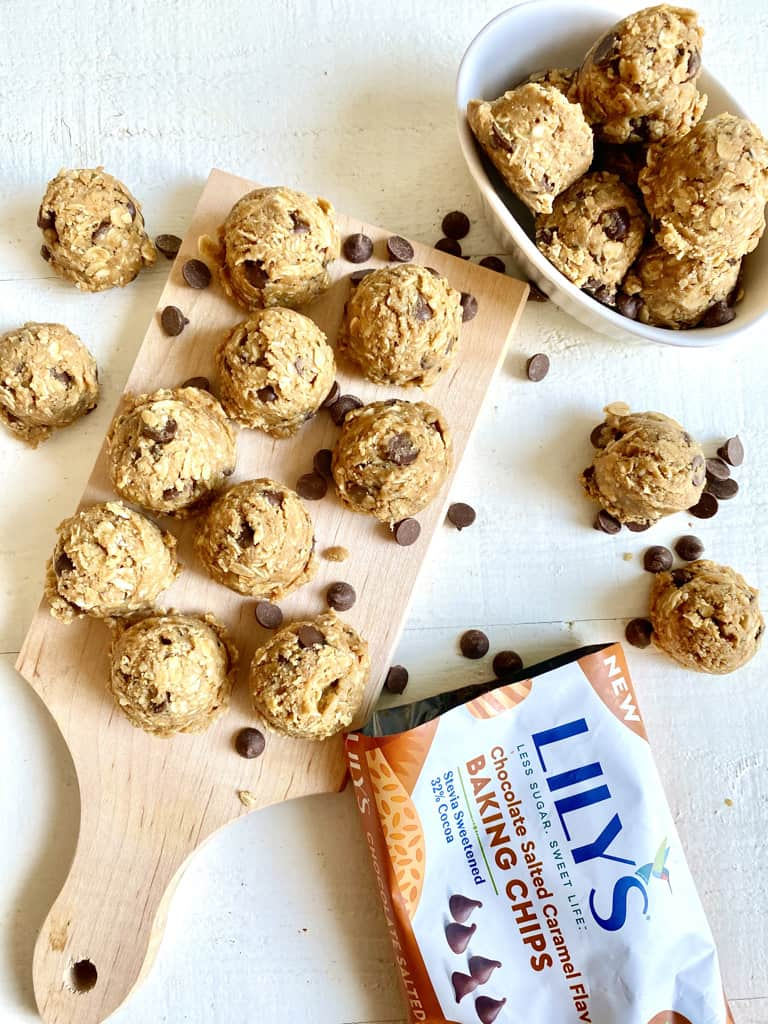 oatmeal protein balls with chocolate chips on wood board with lilys chocolate chips