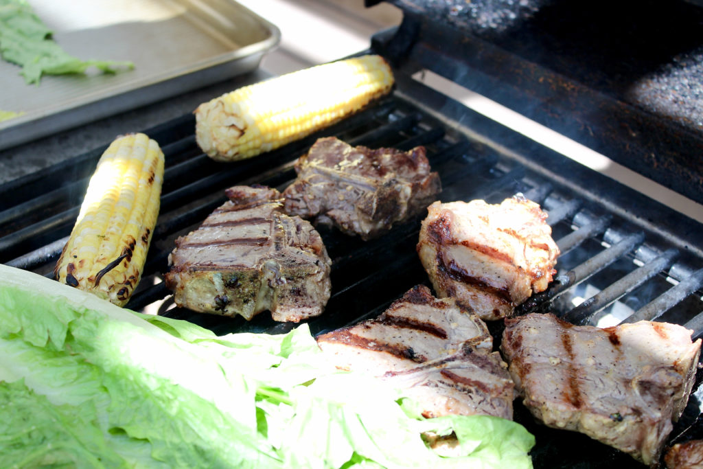 lamb loin chops on grill with corn on the cob and romaine