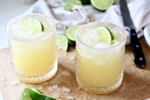 two skinny margaritas with lime wedges on cutting board