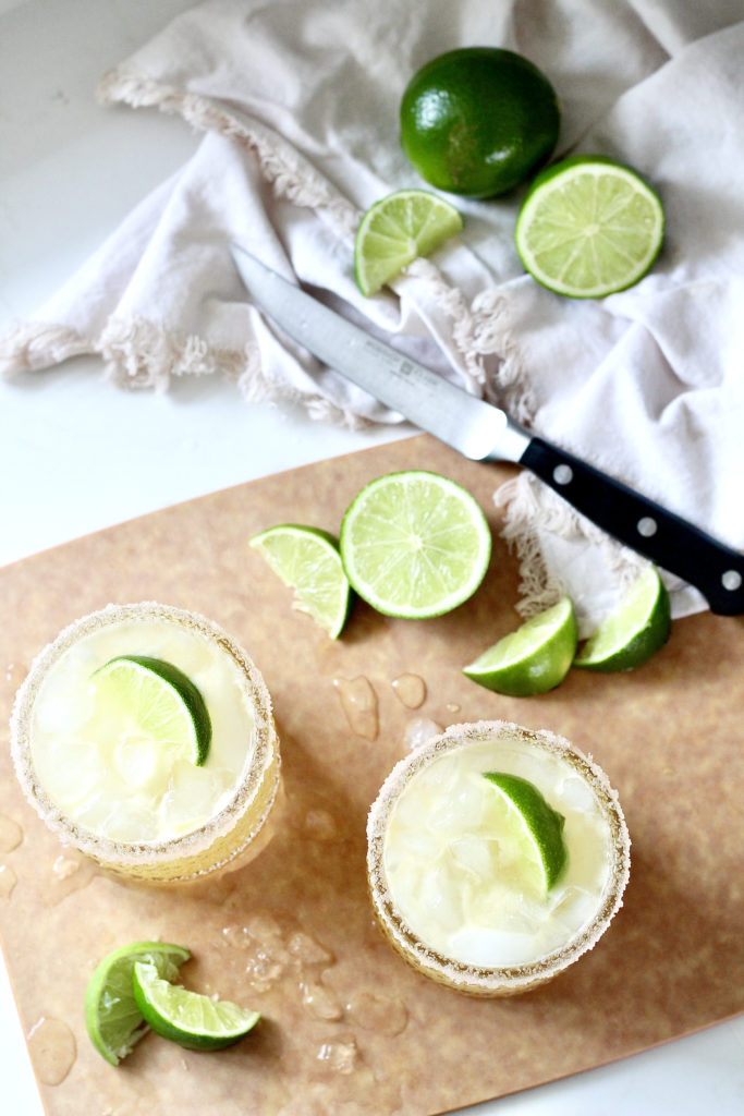 two margaritas on cutting board with limes