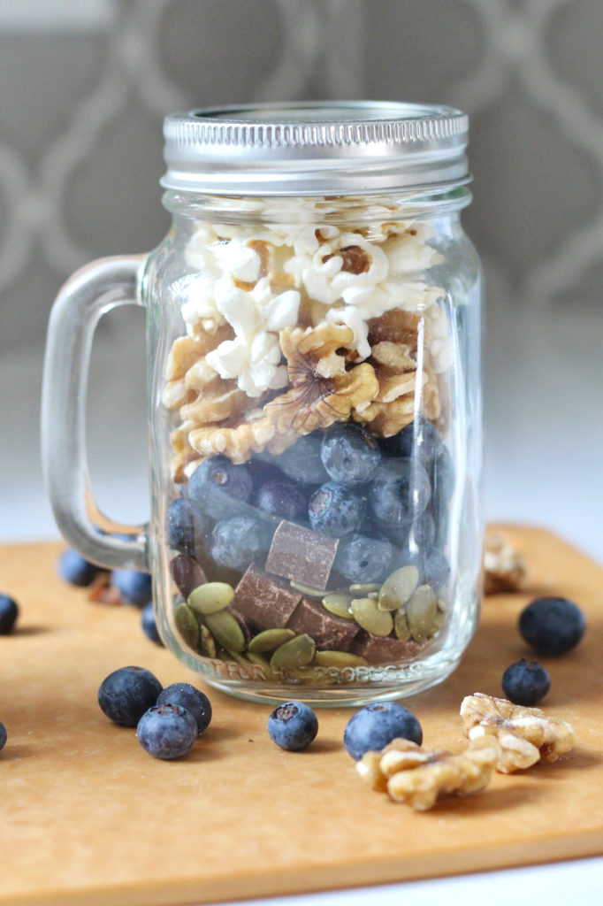 homemade trail mix in mason jar with blueberries walnuts and popcorn