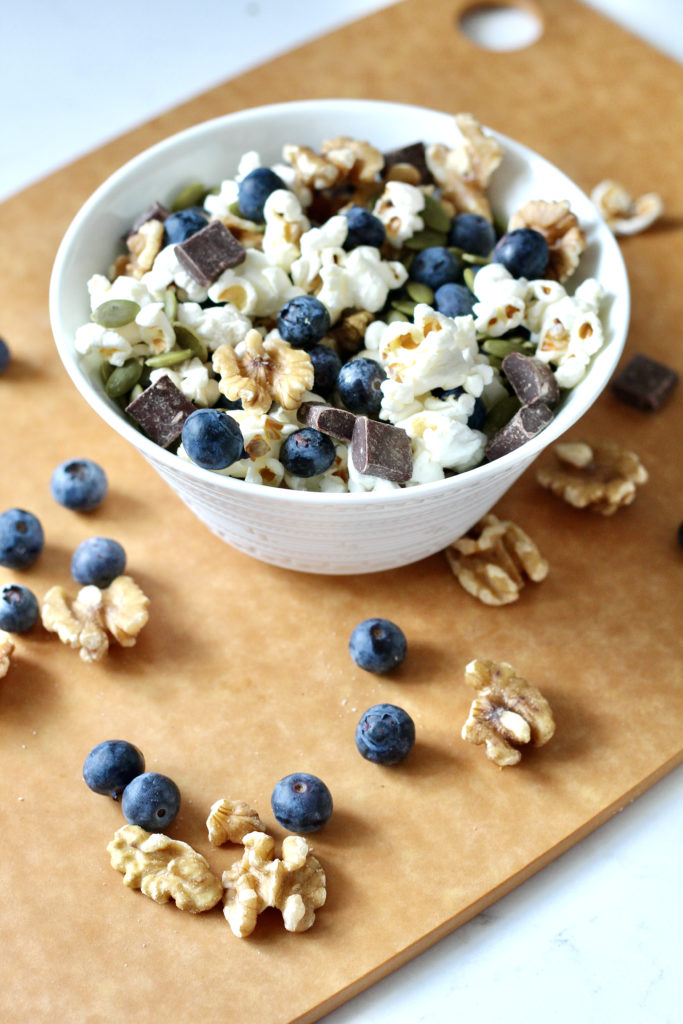 homemade trail mix in white bowl with blueberries walnuts and popcorn