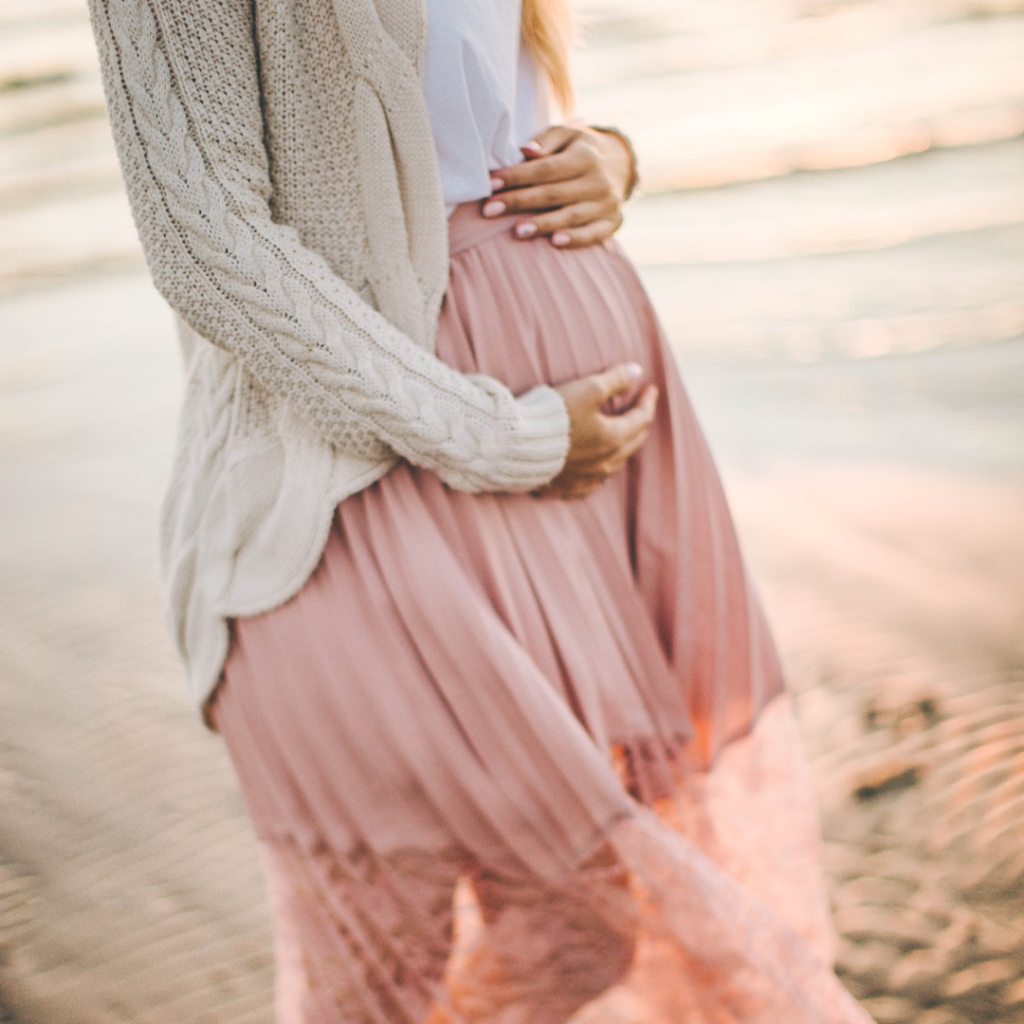 pregnant woman holding belly in pink dress pregnancy and type 1 diabetes
