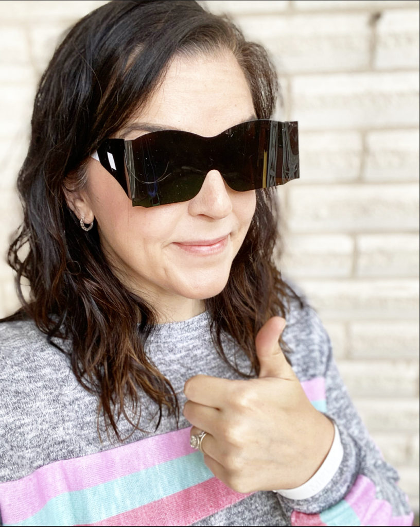 woman after routine eye exam with plastic sunglasses and thumbs up